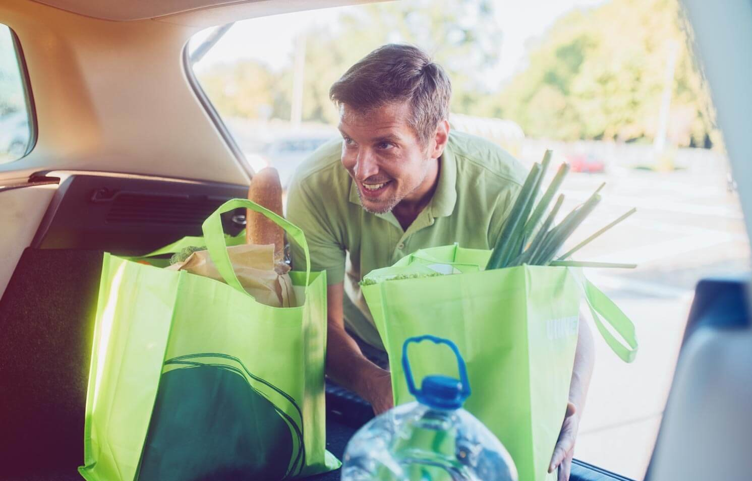 person loading groceries into car